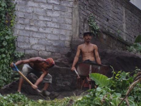 Shoveling wheelbarrows worth of stones and sand