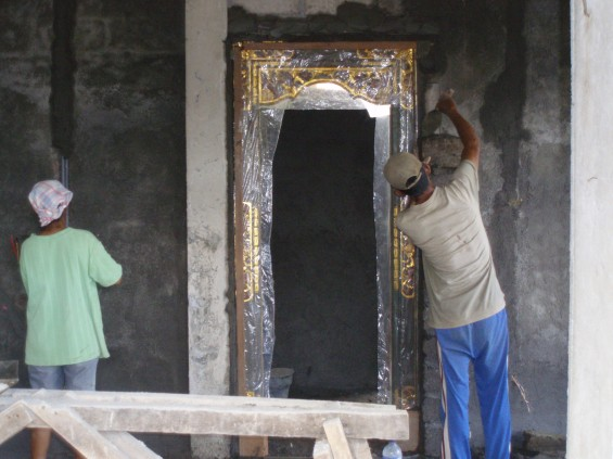 Carefully plastering around the door frame and covering the wiring