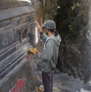 Yaniq giving offerings at the temple by the beach - see the steps behind him