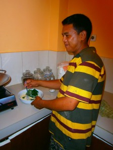 Ketut dipping the bayam into the pancake mix